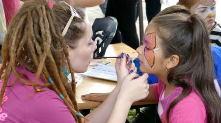 TIMISOARA, ROMANIA - JUNE 01, 2016: Workshop with face painting for children,  in a park in Timisoara, Romania. International children Day. 4K footage.