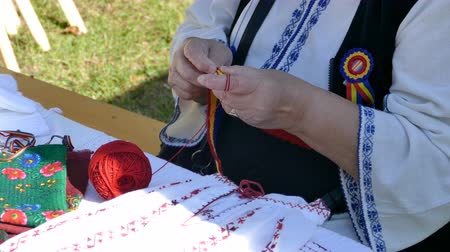 Old woman dressed in romanian traditional clothing, interweaves by hand one belt in national colors and design. Vídeos