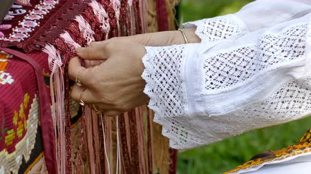 Woman dressed in traditional clothing, interweaves by hand Romanian traditional dress with popular designs.