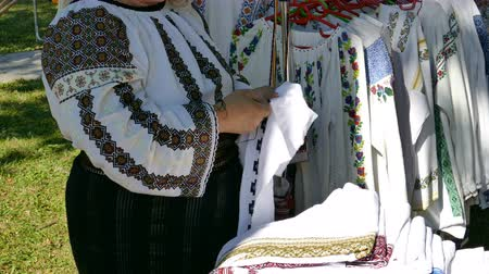 Woman dressed in traditional clothing, sewed by hand Romanian traditional patterns and popular designs on a canvas. Public demonstration at one fair with folk products. 4K footage. Vídeos