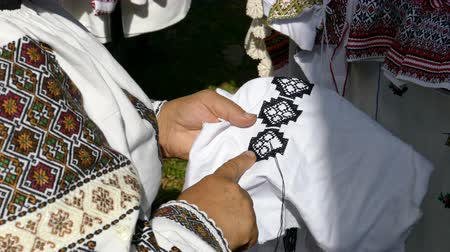 Woman dressed in traditional clothing, sews by hand Romanian traditional patterns and popular designs on a canvas.
