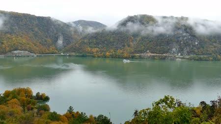 Autumn at the Danube Gorges, the border between Romania and Serbia. View from Serbian part. In the background, on the Romanian bank, the Decebal kings image carved in stone and monastery Mraconia. Vídeos