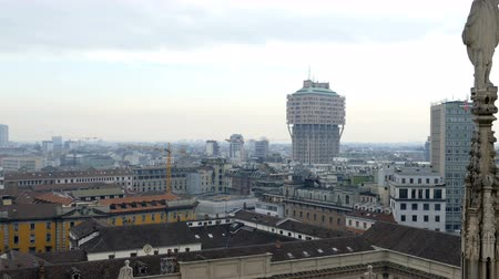 MILAN, ITALY - DECEMBER 11, 2016: View over Milan from the top of the gothic Milan Cathedral, Italy. Churchs roof statues in the foreground, skyscrapers of the city in the background.
