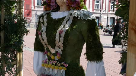 retro revival : TIMISOARA, ROMANIA - APRIL 27, 2018: Floral decoration with a wooden statue dressed in a popular costume made of flowers. Ethnic woman from the Bulgaria. Flower Festival organized by the City Hall. Stock Footage