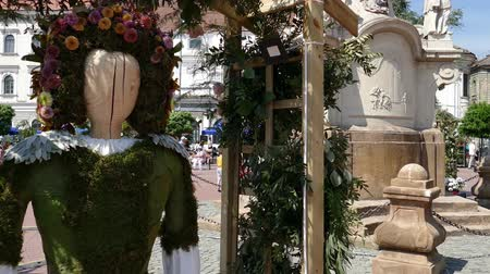 TIMISOARA, ROMANIA - APRIL 27, 2018: Floral decoration with a woman wooden statue dressed in a popular costume made of flowers. Flower Festival organized by the City Hall. Vídeos