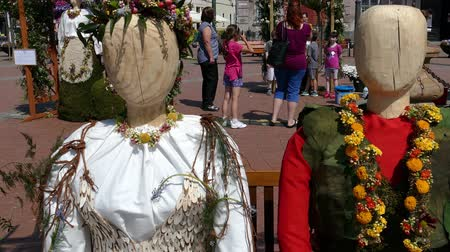 macedonian : TIMISOARA,ROMANIA-APRIL 27,2018:Floral decoration with two wooden statues dressed in a popular costume made of flowers.Italian and Macedonian ethnic women at Flower Festival organized by the City Hall