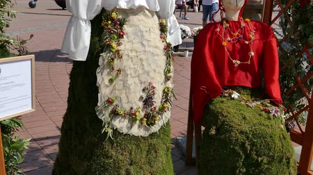 retro revival : TIMISOARA,ROMANIA - APRIL 27,2018:Floral decoration with two wooden statues dressed in a popular costume made of flowers.Hungarian and Gypsy ethnic women at Flower Festival organized by the City Hall.