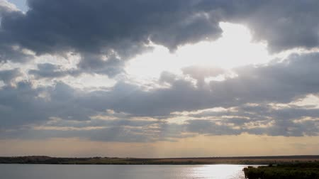 exiting : cloudy scene with sunrays exiting the clouds over an lake Stock Footage