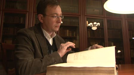 könyvtár : The man flips through an old book