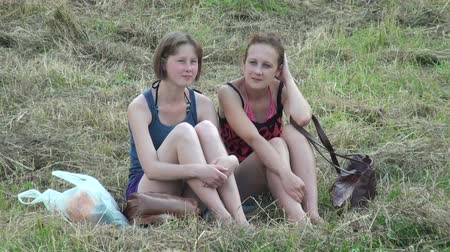 pretty : Two girls friend are sitting on the grass