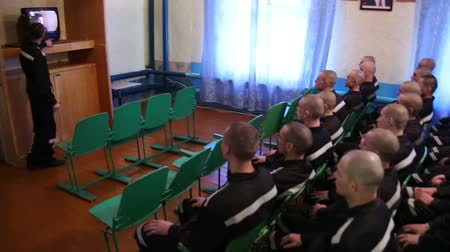 deprivation : A group of prisoners watching the news on television.  Stock Footage