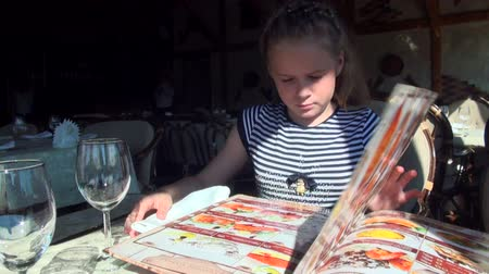 otthonos : Little girl leafing through the menu in the restaurant Stock mozgókép