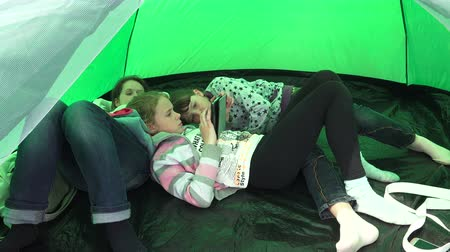 irmãs : Mom and daughters having a rest in a tent. Shot in 4K (ultra-high definition (UHD)), so you can easily crop, rotate and zoom, without losing quality!  Real time. Stock Footage