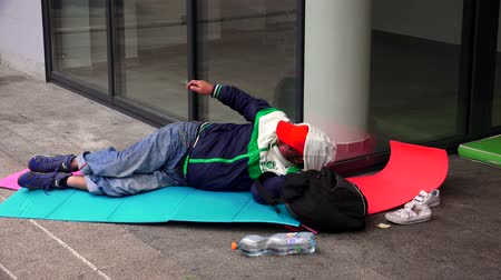 luxúria : BUDAPEST, HUNGARY - AUTUMN 2015: Emigrant, a refugee, sleeping on the street at the train station in Budapest. Shot in 4K ultra-high definition UHD. Stock Footage