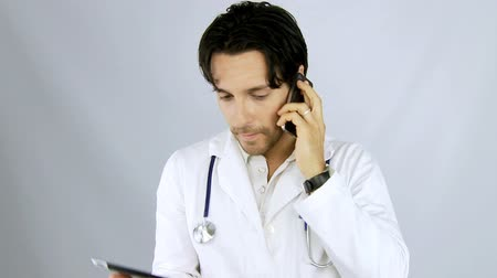 assistência médica : Young handsome doctor on the phone serious Vídeos
