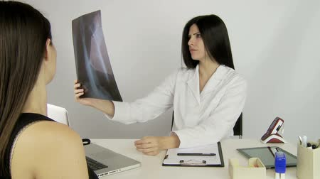 általános : Beautiful doctor looking at x ray of woman patient