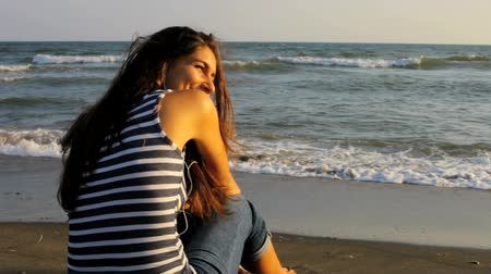 релаксация : beautiful young woman looking sunset on a beach in Italy