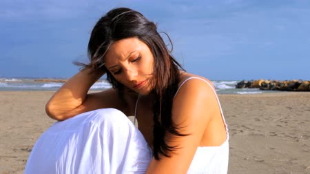 одиноко : Gorgeous woman sitting on the beach sad with wind in her long silky soft hair