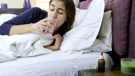 üfleme : Sick woman with flu taking medicine and drinking water