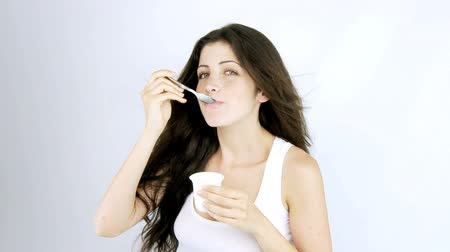 spoons : Beautiful woman eating yogurt on a diet happy