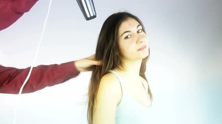 hajápoló : Beautiful female model getting hair dryed by professional hairdresser in studio