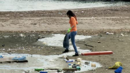 lixo : Girl on dirty beach after hurricane cleaning and picking up dirt Stock Footage