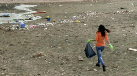 sujo : Beautiful girl with bag ready to clean dirty beach in front of ocean