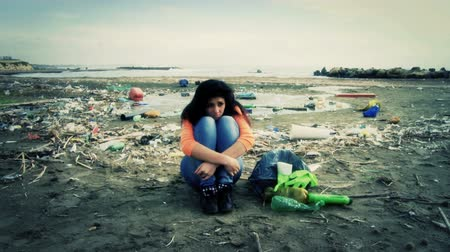 water conservation : Sad girl sitting in total environmental disaster dirt on the beach