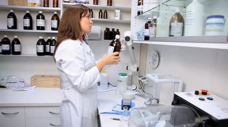 фармацевт : Beautiful female pharmacist putting in order shelf of lab in pharmacy Стоковые видеозаписи