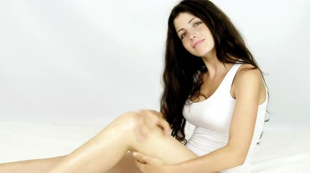krém : Woman with beautiful legs putting cream lotion to make it soft
