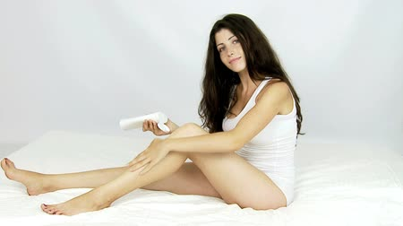 pleťová voda : Happy beautiful woman putting cream lotion on long leg