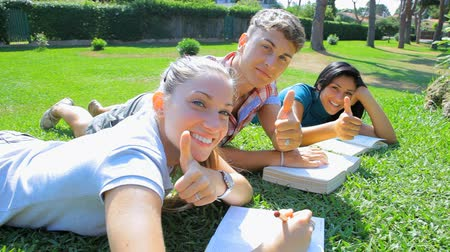 studenci : Students in college smiling showing thumb up while studying Wideo