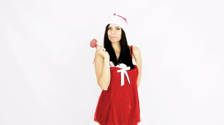 леденец : Gorgeous woman santa claus licking christmas lollipop Стоковые видеозаписи