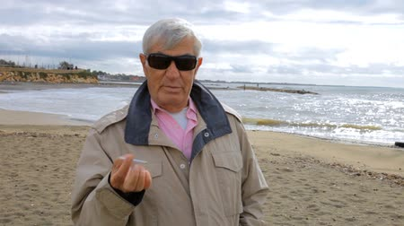 курильщик : Old man relaxing on beach smoking feeling sic coughing scared of lung cancer