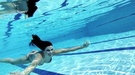 uszoda : Happy gorgeous woman with perfect body swimming underwater