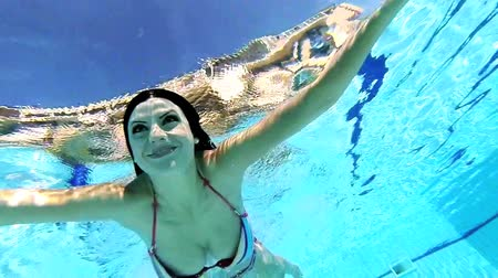 swimming underwater : Happy woman shot from underwater while swimming with bikini Stock Footage