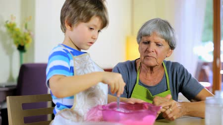 внучка : Happy child cooking with grandmother at home