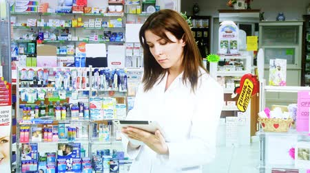 фармацевт : Doctor reading tablet in pharmacy smiling