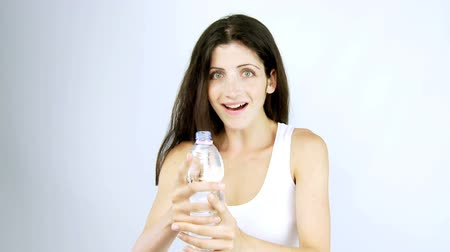 woda mineralna : Woman making funny faces while drinking water