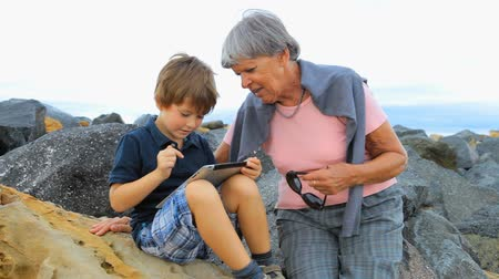 бабушка : Grandmother and grandson playing together outdoors with tablet having fun Стоковые видеозаписи