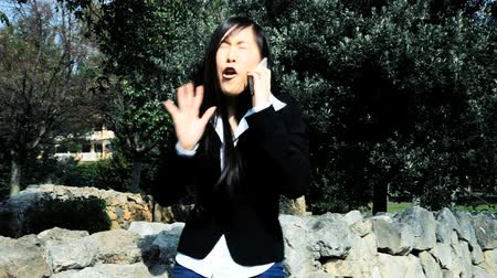 etkileşim : Beautiful chinese business woman medium shot in park angry with phone Stok Video