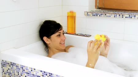 bańki mydlane : Cute female model playing with two ducks in bath tub