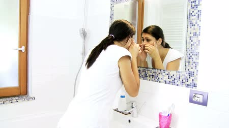 лицевой : Looking at skin in front of mirror in bathroom Стоковые видеозаписи