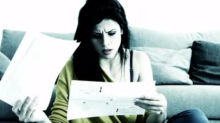 banknoty : Unhappy woman checking bills at home Wideo