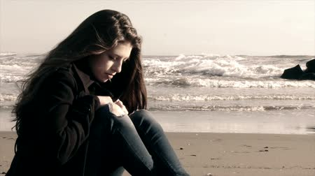 üzgün : Sad girl sitting on the beach in tempest sad slow motion Stok Video