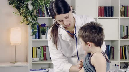 incelenmesi : Nice female doctor visiting cute child Stok Video