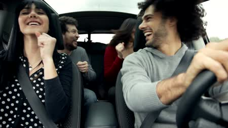 детеныш : Happy group of people enjoying music in car