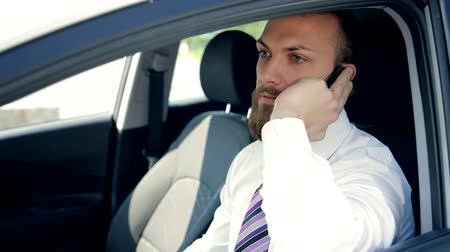 menő : Cool handsome businessman talking on the phone in car Stock mozgókép