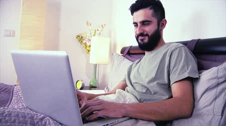 looking : Cool business man in bed in hotel working with pc