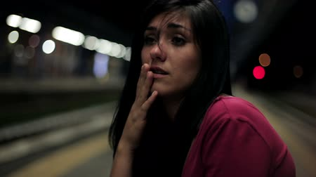 homesick : Young woman at night feeling depressed sitting in train station